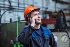 40821854 - the young man working at the old factory on installation of equipment in a protective helmet